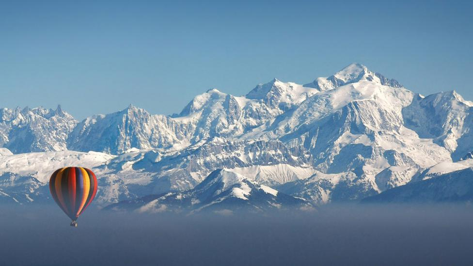 A hot air balllon and the European Alps (Credit: Photographer Chris Archinet/ GettyImages)