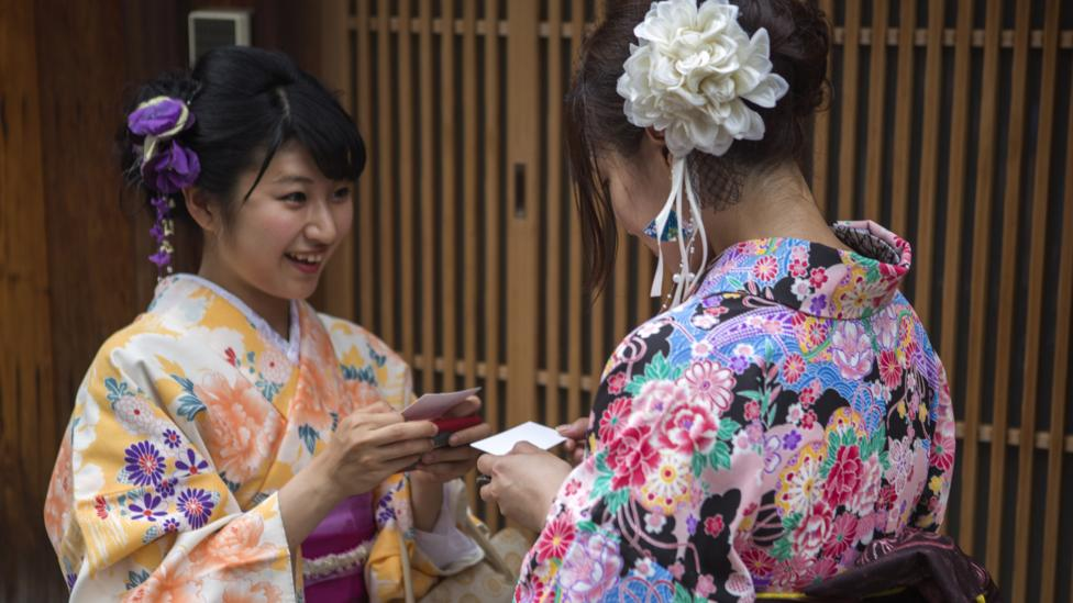 Women wearing traditional kimono costume swap cards in Kyoto, Tokyo, Japan (Credit: Getty Images)