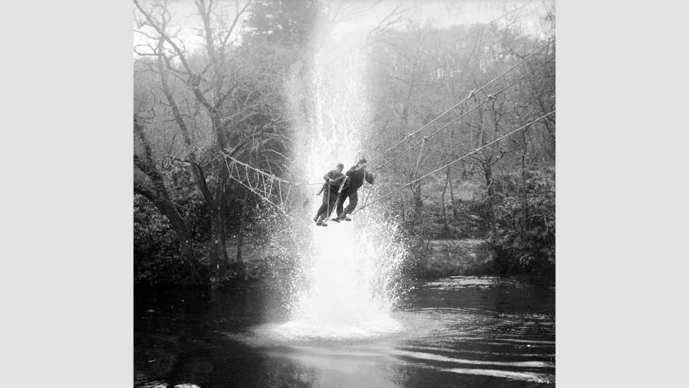 British Commandos cross a river under simulated artillery fire at a training school in Achnacarry, Scotland, in January 1943 (Credit: Imperial War Museum)