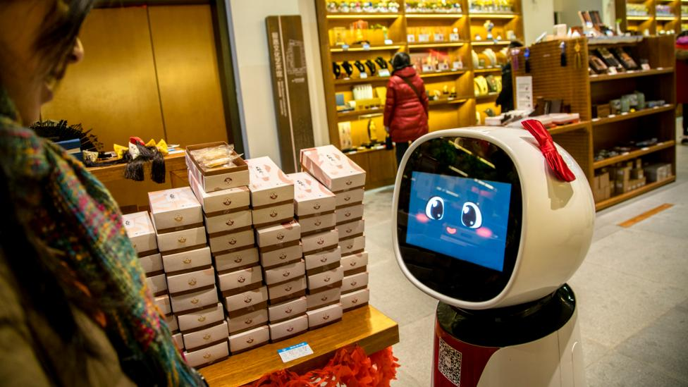 Artificial intelligence will let robots do more complicated jobs, such as this shop assistant serving customers in Japan (Credit: Getty Images)