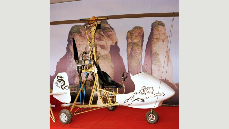 """Xu's autogyro next to a poster of nearby Jianglang Mountain: """"I love flying [there]… I make it to the edge of the mountain and then hover along its ridges."""" (Credit: Xiaoxiao Xu)"""