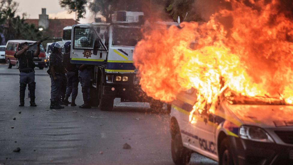 A South African police van is set on fire following protests about inequality in 2016 (Credit: Getty Images)