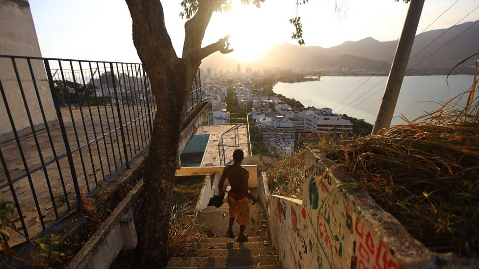 A resident walks in the Cantagalo shantytown in Rio de Janeiro, with the wealthy Ipanema seen in the distance (Credit: Getty Images)