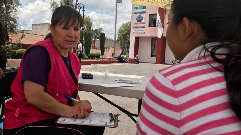 Adriana Chavez, a psychologist with the Instituto de la Mujeres, chats with 12-year-old Raquel Barrera and her parents (Credit: Julissa Trevino)