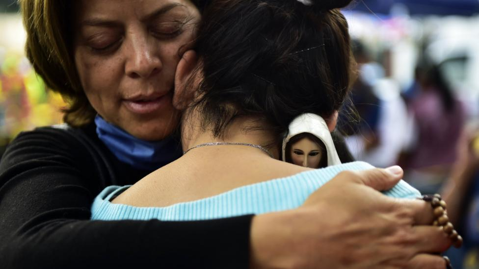 A woman holding an image of the Virgin of Fatima comforts a relative of people who are presumed still buried under the rubble (Credit: AFP/Getty Images)