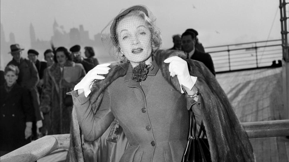 Marlene Dietrich cuts a glamorous figure as she poses in a day suit by Christian Dior on board the Queen Elizabeth in 1950 (Credit: Getty)