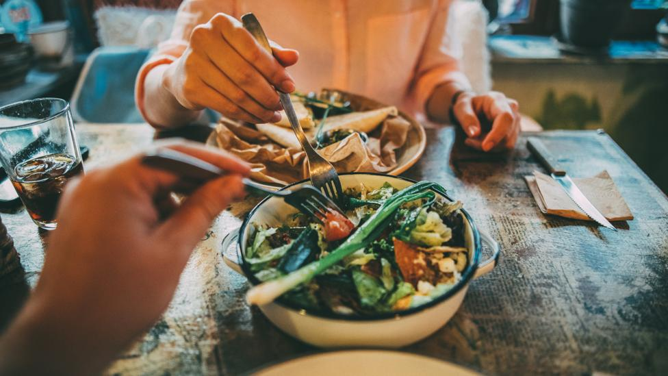 When you eat in company, you might be tempted to order bigger dishes to share (Credit: Getty Images)