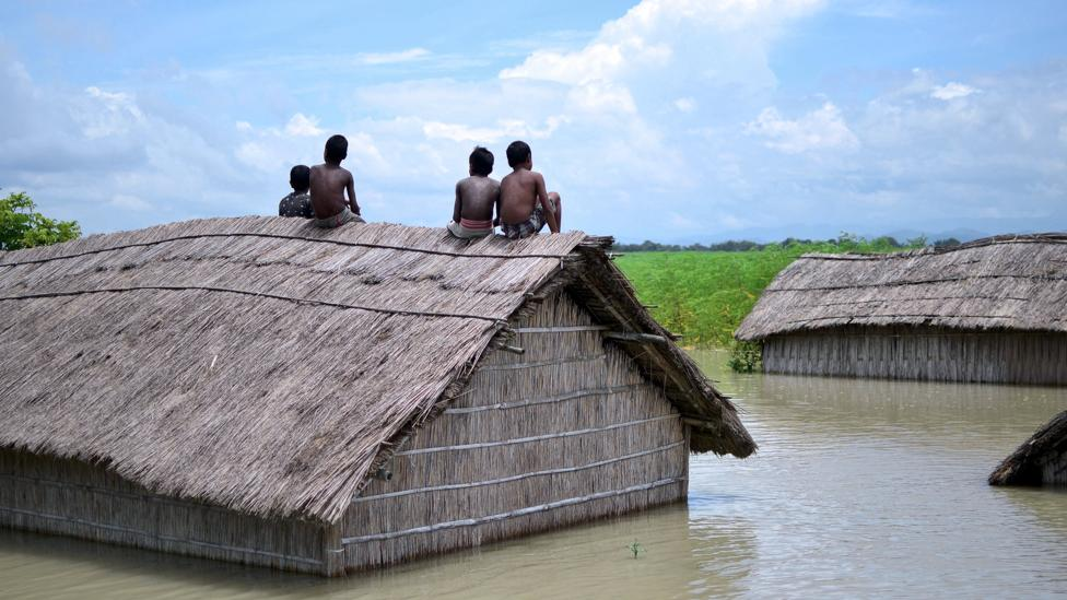 Children sit on the roof of a submerged home after a 2016 flood of the Brahmaputra River in South Kamrup, India (Credit: Getty Images)