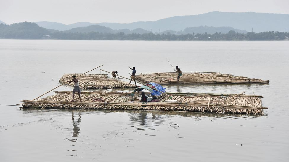 The sapori people paddle rafts on the Brahmaputra River in South Kamrup, India (Credit: Getty Images)