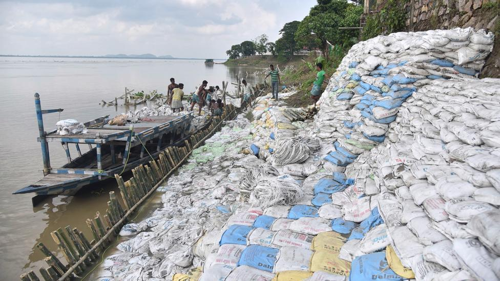 Labourers pile sand bags to try to protect a bank of the Brahmaputra from erosion in Guwahati (Credit: Getty Images)