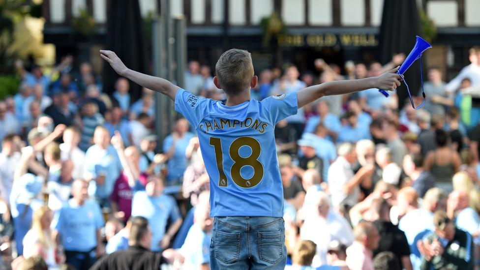 A young Manchester City fan waits with thousands of other fans to watch his team parade the Premier League trophy (Credit: Getty Images)