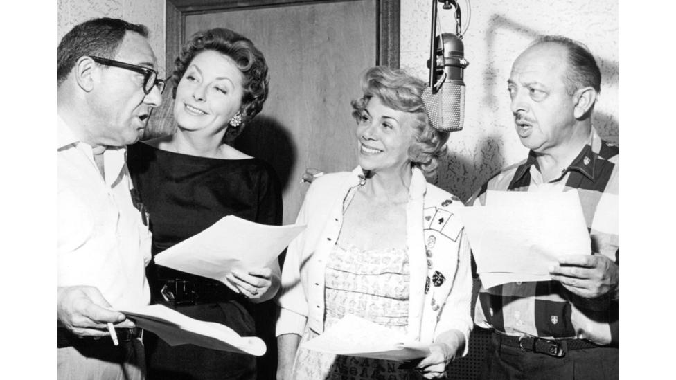 The cast of The Flintstones in a recording session in 1962, including Looney Tunes actor Mel Blanc (far right) (Credit: Getty Images)