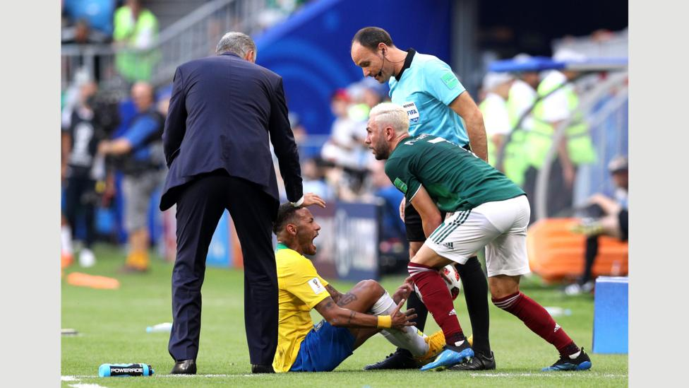 Miguel Layún of Mexico collects the ball as Neymar of Brazil goes down injured during the round of 16 match between Brazil and Mexico on 2 July (Credit: Getty Images)