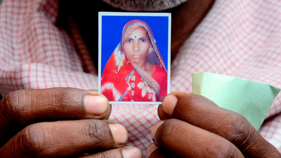 Roop Chand Srivastava holds an image of his wife Phool Bai, who died during the November 2014 mass sterilisation in Bilaspur (Credit: Getty)