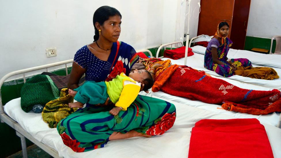 One of the women who suffered complications during the 2014 mass sterilisation that killed 13 women, Anita Bai tends to her child while under care in hospital (Credit: Getty)
