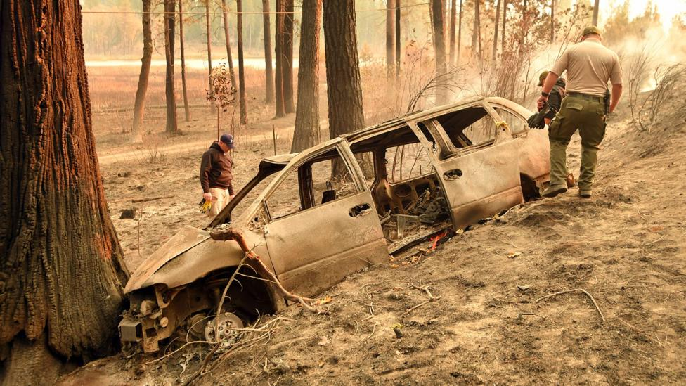 County sheriff officers inspect a vehicle for remains; fires like this one, the Camp Fire, are too fast to be managed (Credit: Getty)