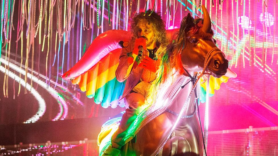 Wayne Coyne of The Flaming Lips riding a fake unicorn on stage is just one example of the recent resurgence of unicorns in popular culture (Credit: Getty)