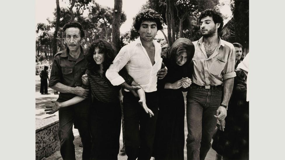 A Lebanese family leaving the Martyrs Cemetery, Beirut, 1976: McCullin makes sure he is close enough so that people know they're being photographed, gaining unspoken permission