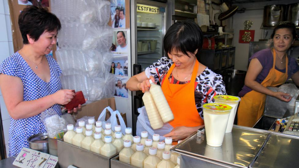 A woman purchases soy milk in Hong Kong. Dairy can make many people feel sick in Asia, where the lactase persistence trait is uncommon (Credit: Getty)