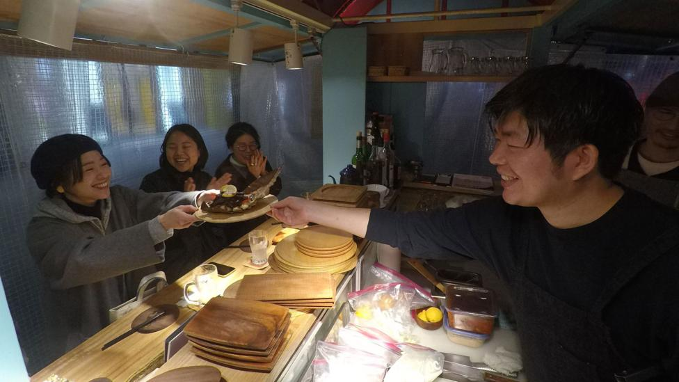 A smiling stall holder hands his happy customers a plate of food (Credit: Edd Gent)