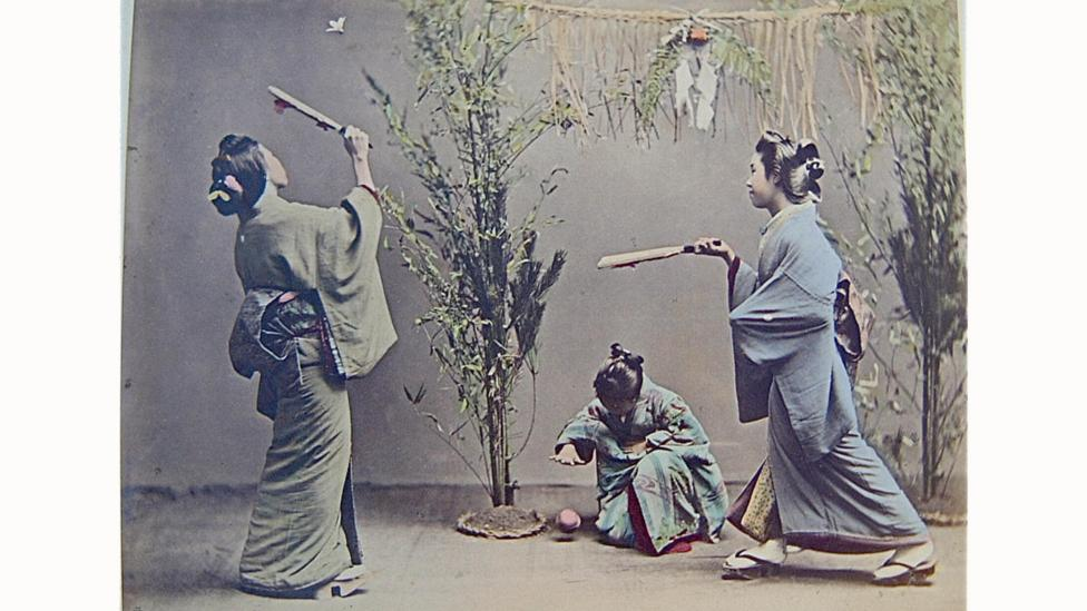 An old photograph of three girls in traditional kimonos playing in a courtyard