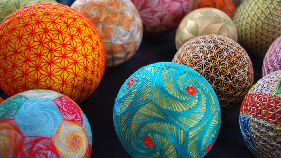 Brightly coloured thread balls in blue, red and oranges