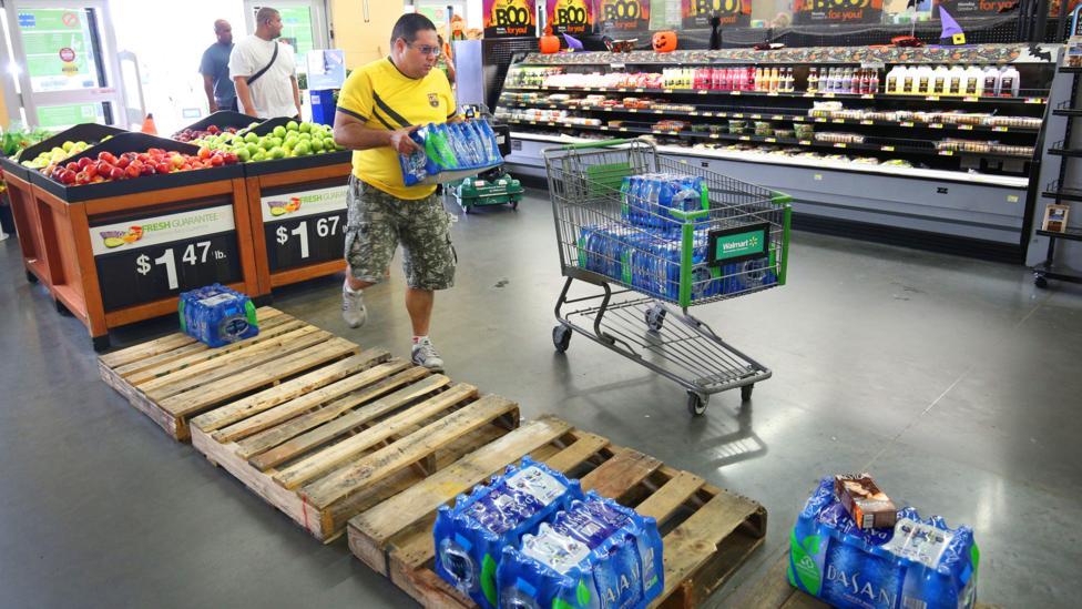 Man picking up bottled water in supermarket