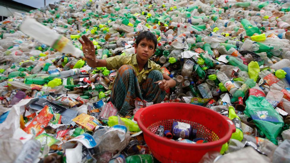 A Bangladeshi child sifts through waste (Credit: Getty Images)