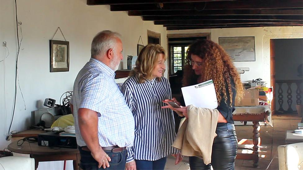 Rosy Costoya (right) speaks with potential buyers.