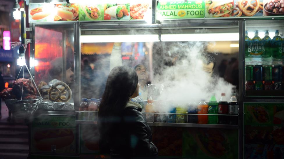 A woman waiting for food being prepared at a street stall (Credit: Getty Images)