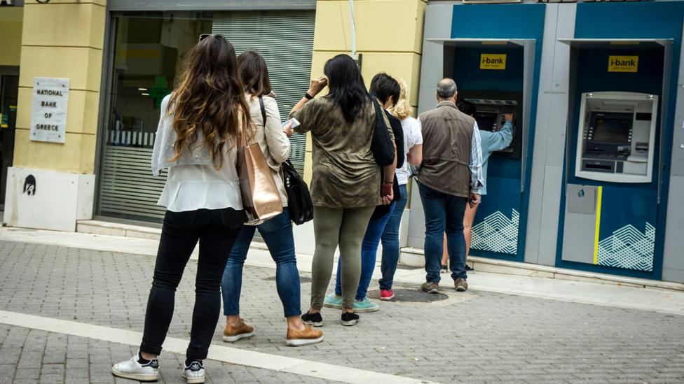 A queue of people waiting to use an ATM (Credit: Alamy)