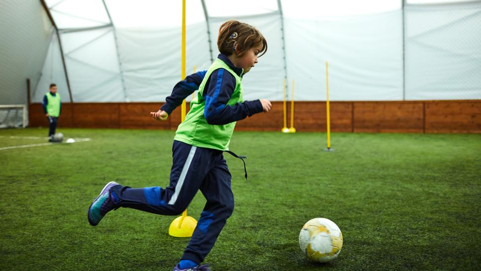 Young boy with a cochlear implant playing football (Credit: Getty Images)