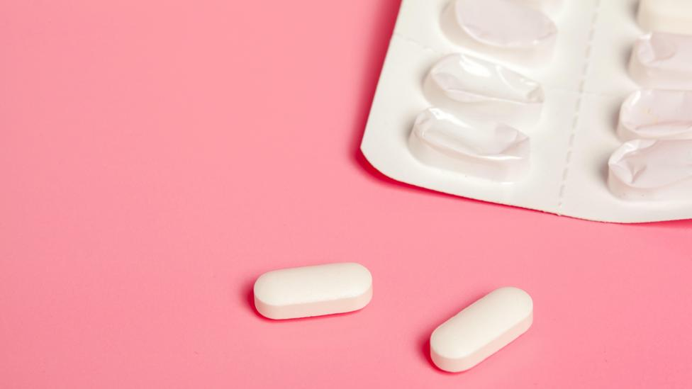 Some pills and a packet on a pink background (Credit: Alamy)