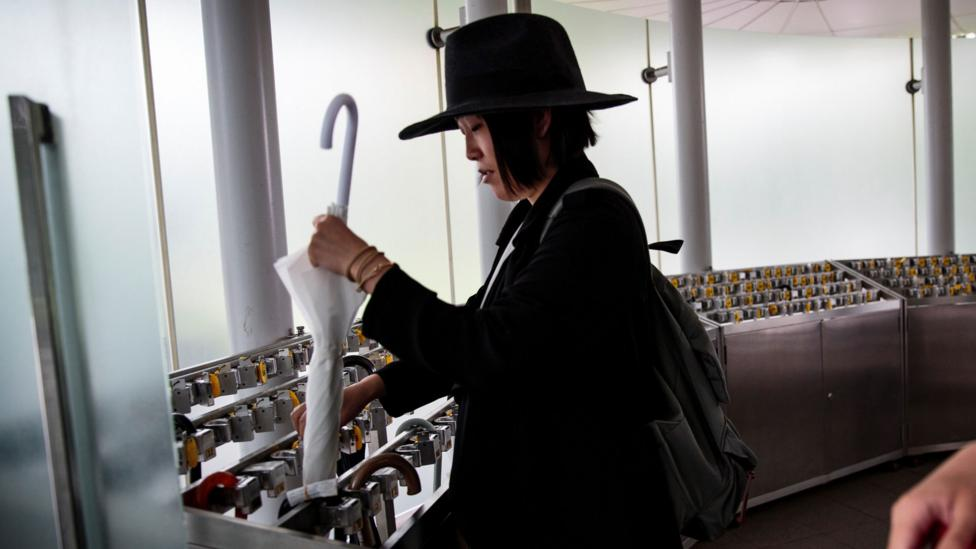 A tokyo resident uses an umbrella lock-up (Credit: Getty Images)