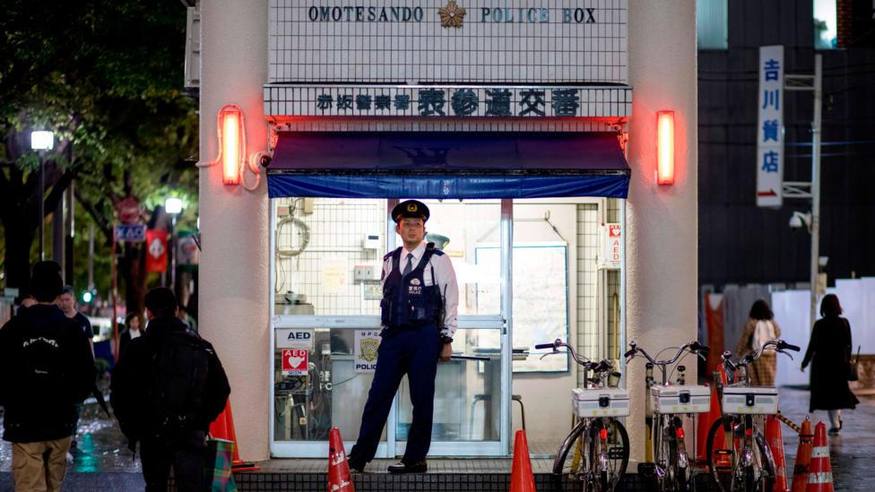 A police officer stands guard outside a police box in Tokyo (Credit: Getty Images)