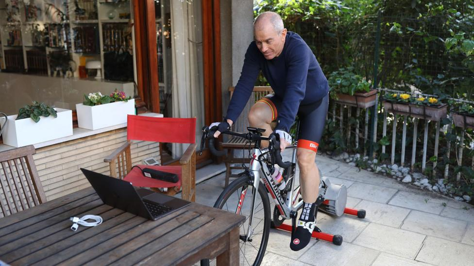 A cyclist in Italy trains at home on a stationary bike to avoid leaving his home as the country continues a nation-wide lockdown amid the Covid-19 pandemic (Credit: Getty Images)