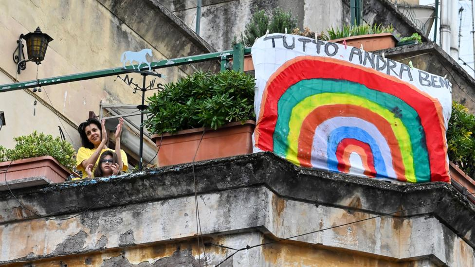 People wave next to a banner reading Tutto Andra Bene (Credit: Getty Images)