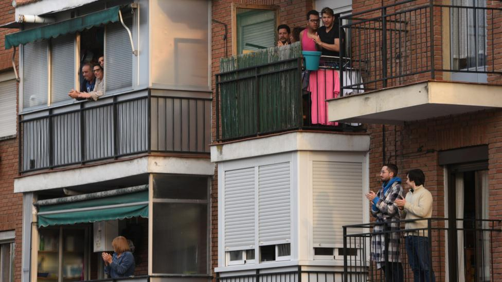 Residents applaud healthcare workers from their balconies in Madrid on 29 March 2020