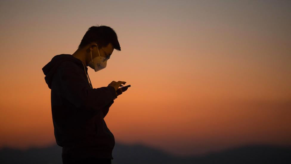 A man on his phone in front of a sunset (Credit: Getty Images)