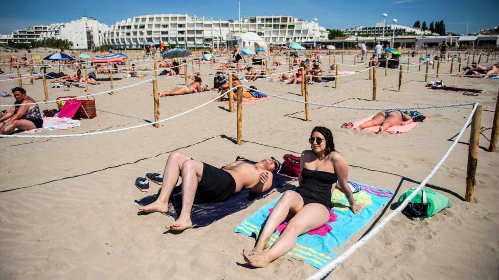 People sunbathe in a roped-off distancing zone at a beach in southern France (Credit: Getty Images)