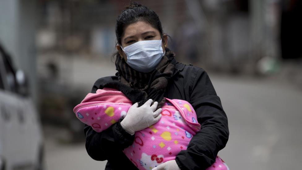 A woman carrying her child to be vaccinated (Credit: EPA)
