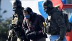 A bearded man, blindfolded, with ear protectors and his hands bound in heavy mitts, is escorted by heavily armed police in full tactial gear, faces hidden by balaclavas