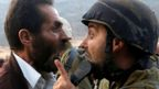 A Palestinian man and an Israeli soldier argue
