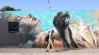 A couple walk past an art work by German artist @norm_abartig and South African artist @dekor as part of the Westdene Graffiti Project in downtown Johannesburg, South Africa, 09 October 2018.